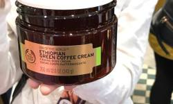 A large circular black tub full of some white cream and a lolly stick that has a black the body shop logo and spa of the world Ethiopian Green Coffee Cream written in black writing on it, on a bright background.