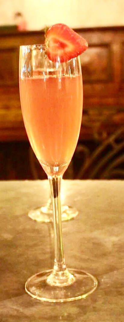 A large champagne flute full of some pale pink coloured liquid and a strawberry on the Rim of the glass on a light brown wooden table, on a dark background.