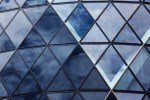 A multi-tonal Blue coloured glass wall with a diamond pattern all over it, on a light background.