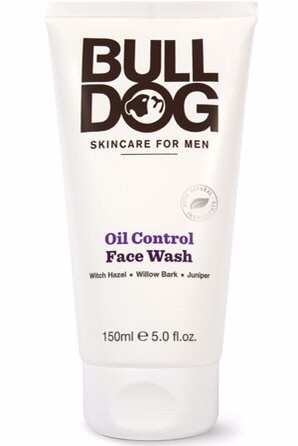A medium thin conical shaped white bottle with a thick white circular lid and a label that has bulldog written in large black writing and skincare for men oil control face wash written in smaller black writing on it, on a white background.