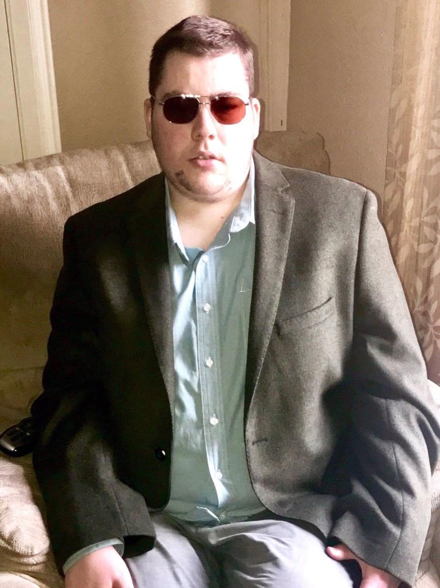 Me sat wearing a dark green blazer and a light green shirt, on a light background.