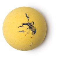 A bright yellow coloured spherical bath bomb with some blue cornflowers sprinkled on top of it, on a white background.