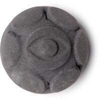 A black coloured spherical bath bomb with some hexagonal detailing and an eye engraved in the top of it, on a white background.