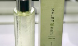 A tall clear glass cylindrical bottle that has a silver lid and a label that has Malee written in large black writing and verdure moisturising oil written in smaller black writing on it next to a tall silver rectangular box that has Malee written in large black writing and Verdure moisturising oil written in smaller black writing on it, on a bright background.