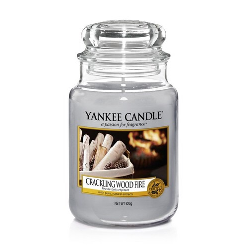A tall glass jar full of some light blue coloured wax with a label that has yankee candle written in white writing, Crackling Wood Fire written in black writing, and a picture of some light blue coloured wood in a square pot next to a roaring wood fire on it, on a white background.