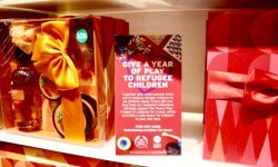 Two tall red gift boxes with a red and gold tied ribbon on the top of them sandwiched between a bright red card that has Give A Year Of Play To Refugee Children written in bright bold white writing on it on a rectangular clear glass shelf, on a bright background.