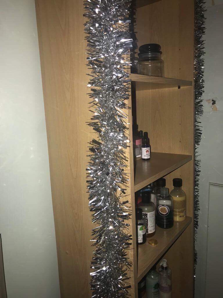 Some shiny silver tinsel wrapped around a tall light wooden rectangular bookcase filled with some various different shaped bottles, on a light background.