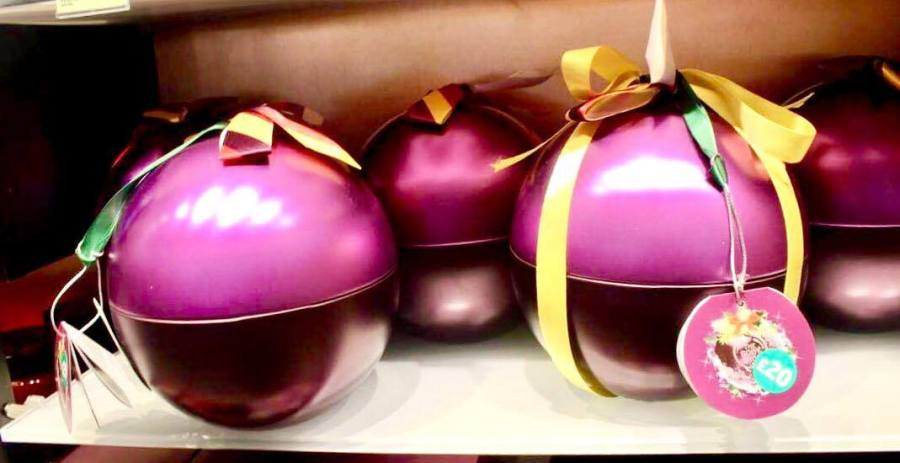 Two large spherical metallic purple Plums with some bright green ribbon on top of them on a rectangular clear glass shelf, on a light background.