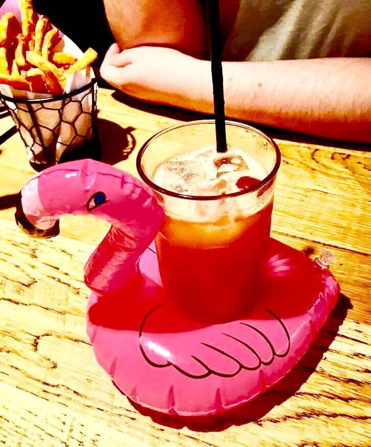 A tall clear glass full of some bright pink liquid and some cubes of ice inside a miniature Pink Flamingo shaped pool float on a light wooden table, on a light background.