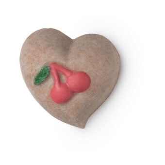 A large dark Pink heart shaped body scrub bar that has a picture of a Cherry with a green stork engraved into the top of it, on a white background.