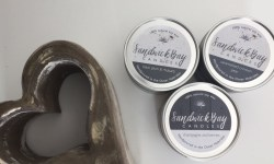three small silver metal jars full of some white coloured wax with some white labels that have Sandwick Bay Candles Caramelised Crimson Pear, Black Plum & Rhubarb, and Champagne & Berries written in bold grey writing on them next to a ceramic brown heart ornament, on a light grey background.