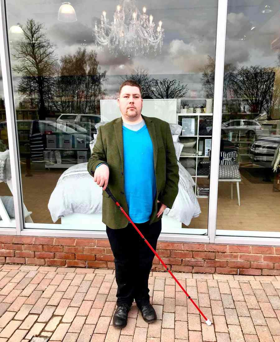 me stood on some grey stone paving in front of a large rectangular window wearing a medium green jacket, a bright blue jumper, a pair of black trousers, and a pair of black Leather boots holding a long red cane, on a light background.
