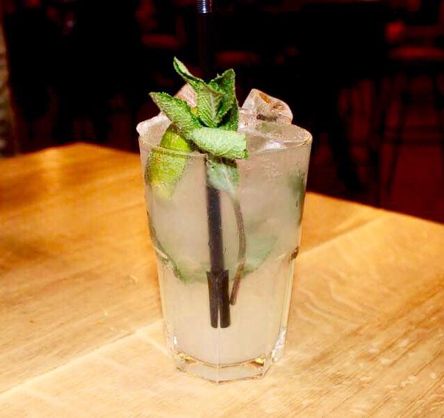 A tall high ball glass full of some clear liquid, some clear ice cubes, some mint leaves, some slices of Lime and a black straw on a light wooden table, on a light background.