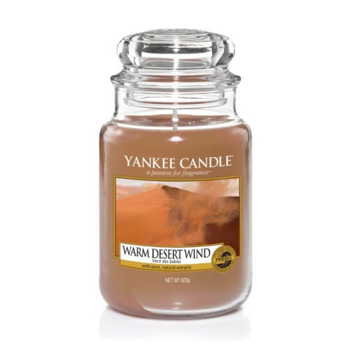 A tall glass jar full of some light Gold coloured wax with a label that has yankee candle written in black writing, Warm Desert Wind written in black writing, and a picture of a bright sandy desert below a white misty sky on it, on a bright background.