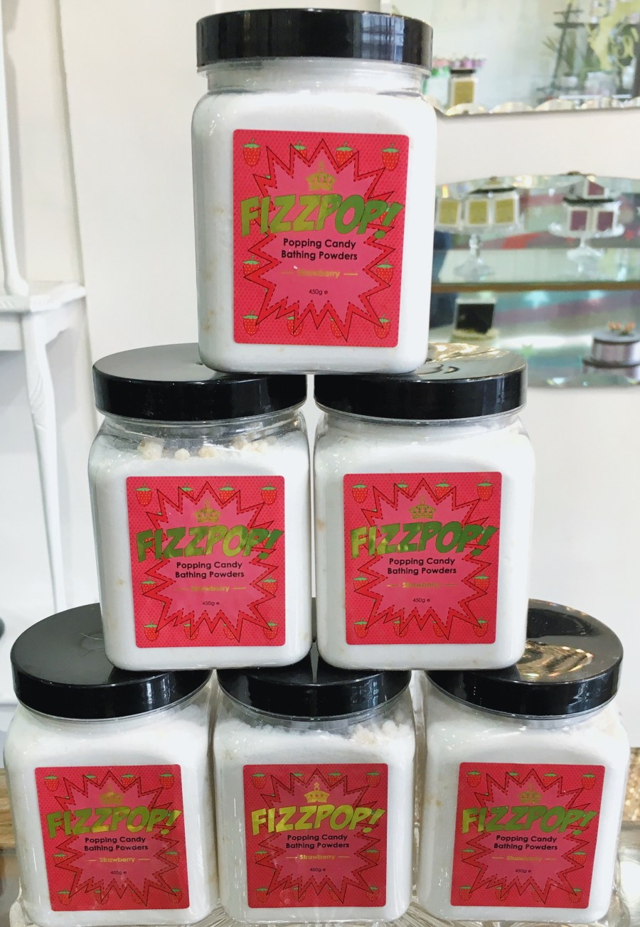 six white square plastic tubs stacked on top of each other with some black lids and red stickers that have fizz pop written in green writing and Strawberry, Banana, Peach, Watermelon and Lychee written in black writing on them, on a white background.