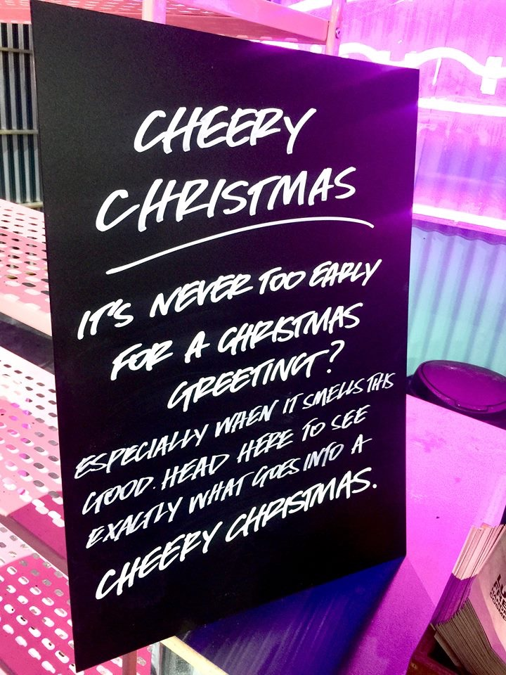 A large black board that has Cheery Christmas written in bold white writing on it, on a white background.