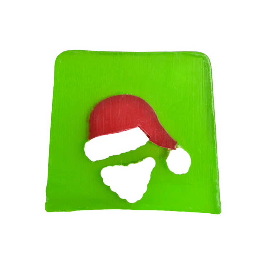 A large square block of bright green soap that has a picture of a Santa wearing a Santa's Hat engraved into it, on a white background.