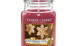 A tall cylindrical Glass Jar full of some dark Pink coloured Wax with a label that has Yankee Candle written in black writing, Glittering Star written in black writing, and a picture of some ornate Star shaped Baubles on it, on a white background.