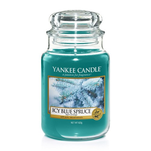 A tall cylindrical Glass Jar full of some turquoise coloured wax with a label that has Yankee Candle written in black writing, Icy Blue Spruce written in black writing, and a picture of a Tree Branch covered in some Snow on it, on a white background.
