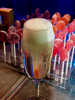 A tall thin Champagne Flute full of some clear Prosecco, a cylindrical lolly pop and some white foam on a rectangular silver table covered in some blue cloth, on a dark background.