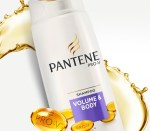A tall rounded rectangular white plastic bottle with a white lid and a purple label that has Pantene Pro-V Volume & Body Shampoo written in bold white writing on it, on a white background.