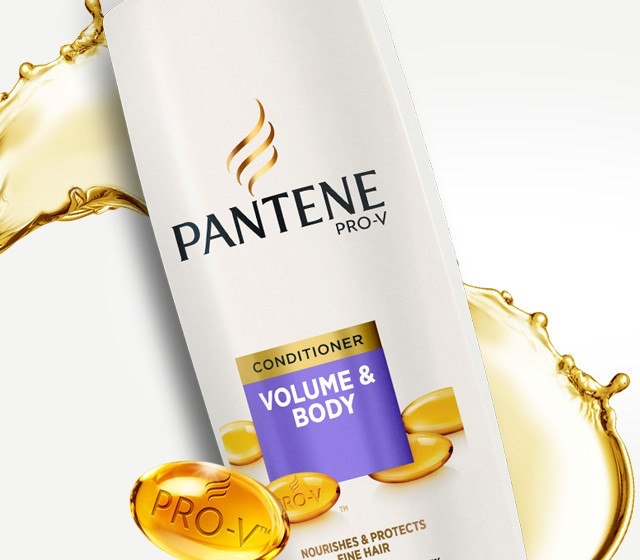 A tall rounded rectangular white plastic bottle with a white lid and a purple label that has Pantene Pro-V Volume & Body Conditioner written in bold white writing on it, on a white background.