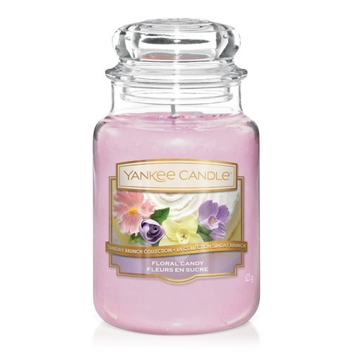 A tall glass jar full of some dark pinky purple wax with a label that has Yankee Candle written in gold writing, floral candy written in white writing, and a picture of some different coloured flowers on it, on a white background.