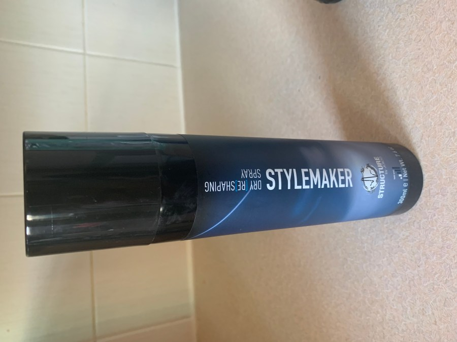 a tall cylindrical Black Plastic Hairspray Can with a white label that has Structure by Joico Stylemaker written in dark blue writing on it, on a white background.
