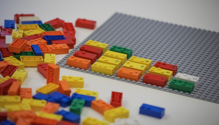 Some different coloured Lego Bricks embossed with Braille dots, on a white background.