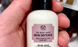 A short cylindrical white plastic spray bottle with a black lid and a bright pink label that has The Body Shop Skin Defence Multi-Protection Face Mist SPF30 PA++ written in bold black writing on it, on a white background.