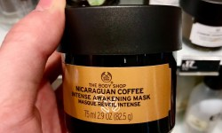 A short cylindrical clear glass jar full of some dark brown liquid with a black lid and a bright gold label that has the body shop nicaraguan coffee Intense awakening mask written in bold black writing on it, on a white background.