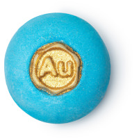 A small spherical shaped bright blue bath bomb covered in some gold lustre with a circular disk of cocoa Butter embedded on top of it that has AU written in bold black writing on it, on a white background.