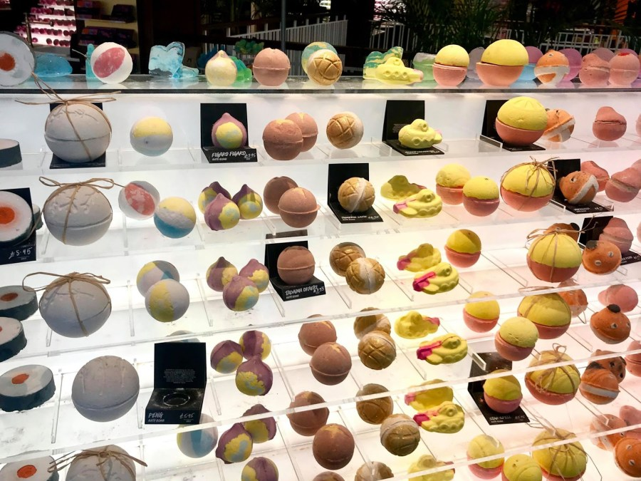 Three large rectangular clear glass shelves full of some various coloured spherical Bath Bombs, on a bright background.