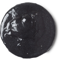 A small circular puddle of black shower slime with some little pieces of grit in it, on a white background.