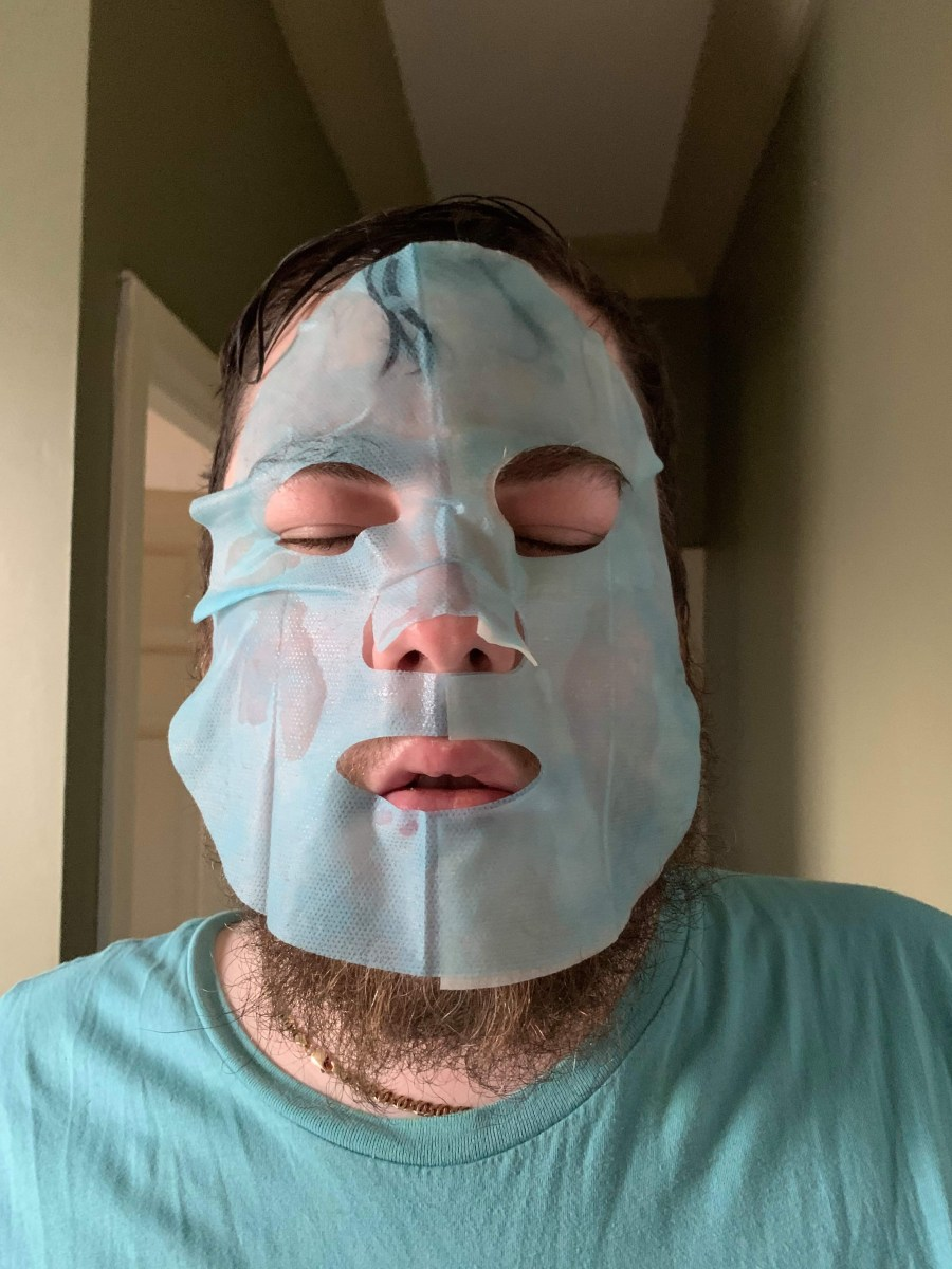 A bearded man wearing a large light blue sheet mask stood against a light green wall.