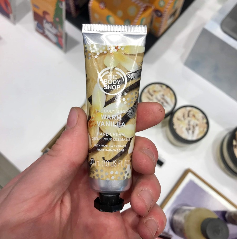 A small thin conical silver plastic tube with a black lid that has the body shop warm vanilla hand cream written in bold white writing and some pictures of some vanilla pods on it, on a white background.