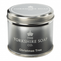 A short cylindrical silver tin with a bright pink label that has The Yorkshire Soap Company Christmas Tree Tin candle written in bold white writing on it, on a white background.