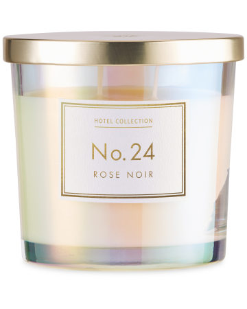A medium cylindrical clear glass jar full of some bright white wax with a shiny gold metal lid and a white label that has Aldi Hotel Collection Rose Noir Candle written in bold gold writing on it, on a white background.