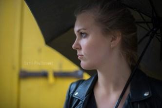 Portait d'une jolie jeune fille blonde sous un parapluie. L'artère plan est jaune. © Lumi Poullaouec