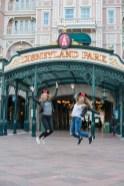 Deux jeunes filles blondes heureuse sautant devant l'entrée du parc Disneyland Paris. ©Lumi Poullaouec