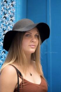 Portrait d'une jeune et jolie fille blonde aux yeux bleus posant avec un chapeau noir. Arrière-plan bleu. ©Lumi Poullaouec