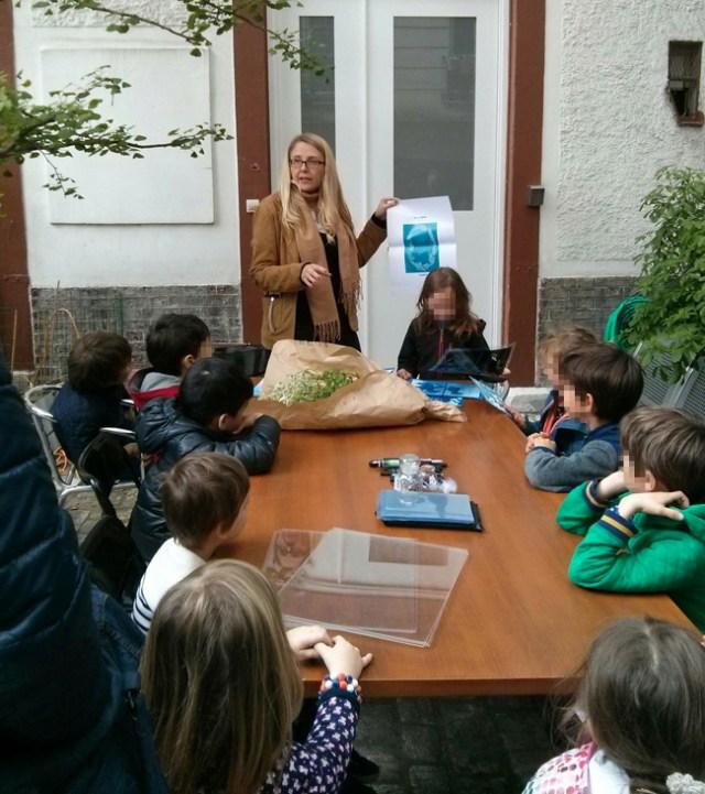 Photo de Lumi Poullaouec entourée d'enfants lors de l'atelier cyanotype à la galerie.