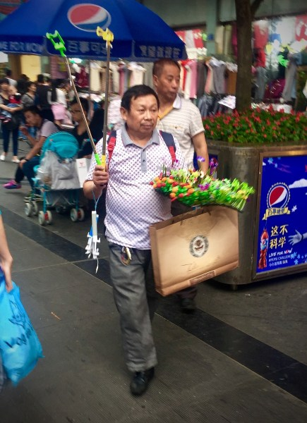 This man is selling little flowers and weeds... for your hair. Oh, and selfie sticks, of course.
