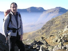 Kevin Brown on Crinkle Crags, with Sca Fell and Scafell Pike