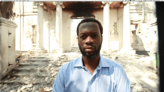 Pras Michel stands in front of crumbled palace