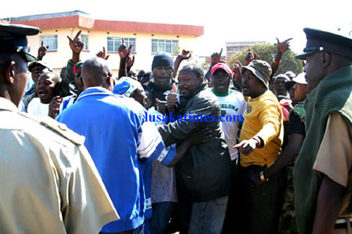 Police officers block suspected MMD cadres from accessing the Lusaka magistrate court where they wanted to go and clash with their PF counterparts.