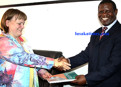 """Local government and housing Deputy Minister Hon. Chrispine Musosha receives a book """"Guide to the Draft Urban and Regional Planning Bill"""" from Embassy of Sweden charge d 'affaires Charlotta Norrby in Lusaka"""