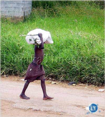 A Child carrying a heavy load in Ndola where child labour is on the rise