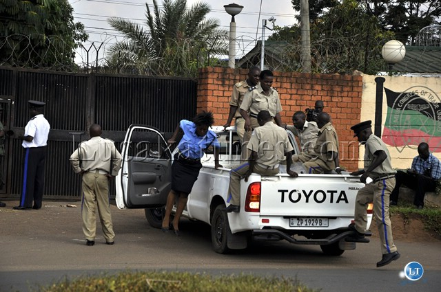 Police officers arrive at the former Taskforce on corruption offices in Lusaka