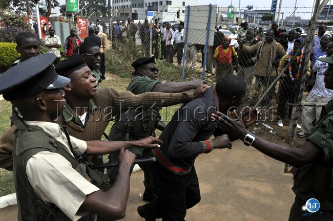 Police officers manhandle a UPND cadre